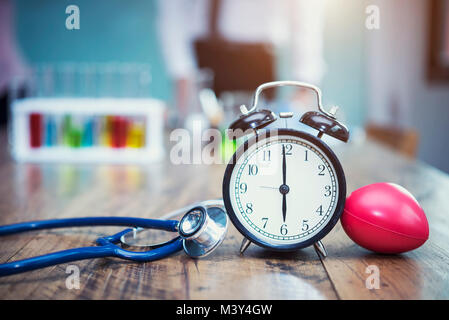 Healthy checking plan concept. Alarm clock with medical instruments stethoscope and red heart on wood table and - Stock Photo