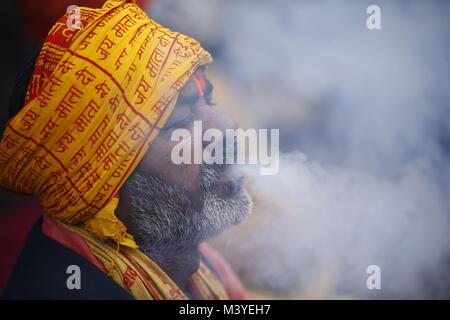 Kathmandu, Nepal. 13th Feb, 2018. A Sadhu or holy man exhales marijuana smoke from a chillum during Maha Shivaratri - Stock Photo