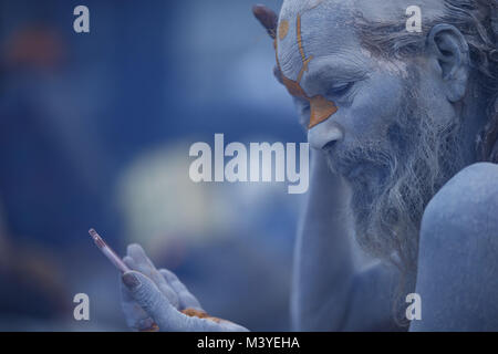 Kathmandu, Nepal. 13th Feb, 2018. A Sadhu or holy man applies color onto his face while getting ready during Maha - Stock Photo