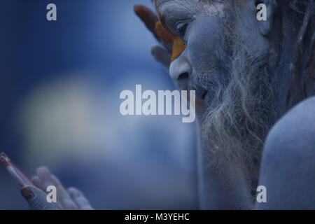 Kathmandu, Nepal. 13th Feb, 2018. A Sadhu or holy man applies color on his face while getting ready during Maha - Stock Photo