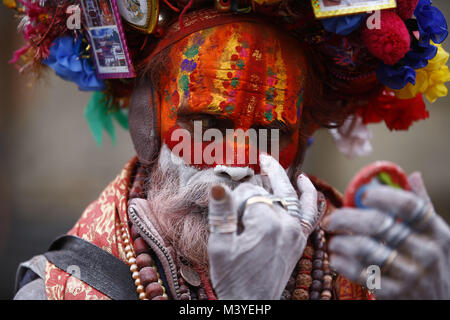 Kathmandu, Nepal. 13th Feb, 2018. A Sadhu or holy man looks at a pocket mirror while getting ready during Maha Shivaratri - Stock Photo