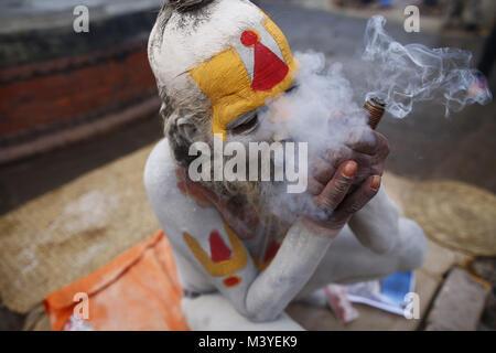 Kathmandu, Nepal. 13th Feb, 2018. A Sadhu or holy man smokes a marijuana chillum during Maha Shivaratri festival - Stock Photo