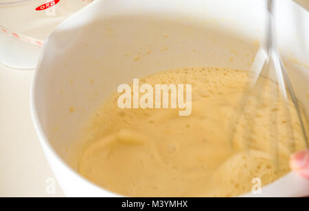 Beating mixture with whisk to make pancake batter for Shrove Tuesday with flour, milk, eggs, and oil in a home kitchen - Stock Photo