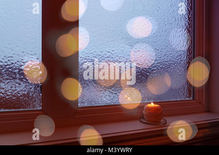 Cozy winter composition with burning candle and bokeh lights. - Stock Photo