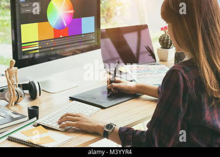 Graphic designer working on creative desk computer while using graphic tablet at desk in the office - Stock Photo