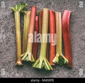 Fresh organic rhubarb stalks on gray granite table , top view. Healthy dieting and antioxidant food - Stock Photo