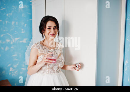 Portrait of a gorgeous bride in her room with perfumes in her hand. - Stock Photo