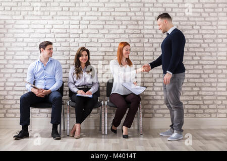 Young Applicant Woman Shaking Hands With Businessman In Office - Stock Photo