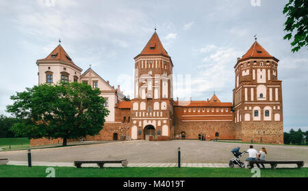 Mir, Belarus - June 25, 2017: Young family with baby sits on bench and admires Medieval castle in Mir, Belarus. - Stock Photo