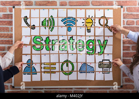 Business People Hands Making Strategy Concept With Adhesive Notes On Corkboard - Stock Photo