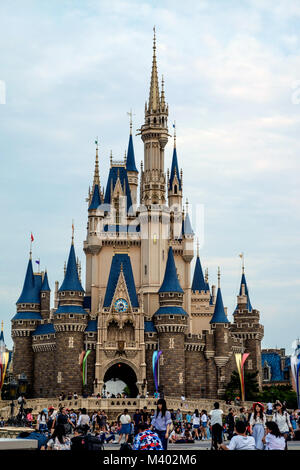 Cinderella castle at Disneyland Tokyo with crowds of people in front. - Stock Photo