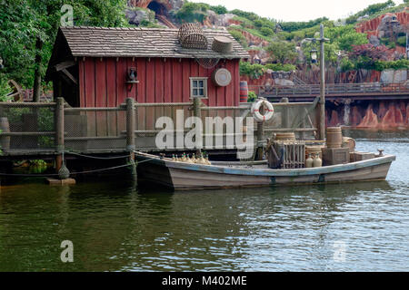 Rustic wooden red hut with boat docked in front on river stocked with supplies. Water in foreground, rocks, hills - Stock Photo