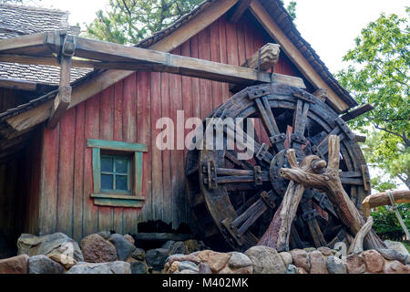 Old wooden water wheel in front of a rustic mill house, with faded red paint. Rocks in the front, trees in the background. - Stock Photo