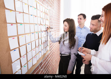 Close-up Of Business People Hands Holding Blank White Notes Notes On Corkboard - Stock Photo