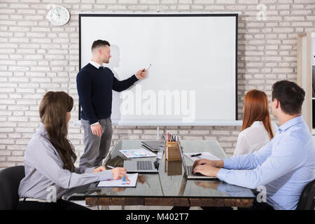Businessman Giving Presentation To His Colleagues In Business Meeting - Stock Photo