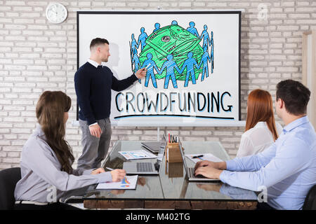 Businessman Showing Crowd Funding Concept On Whiteboard To His Colleague In Office - Stock Photo