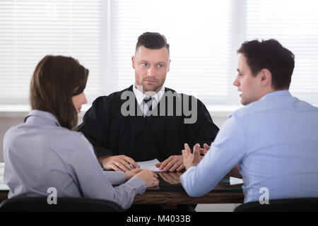 Young Couple Arguing With Each Other In Front Of Judge At Courtroom - Stock Photo