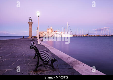 Mandraki harbour and fortress Agios Nicolaos in Rhodes town after sunrise, Rhodes Island, Greece, UNESCO - Stock Photo