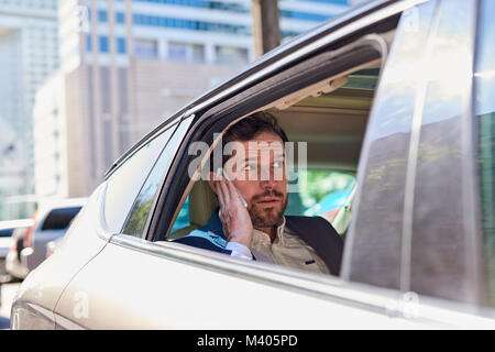 Businessman being driven through the city talking on a cellphone  - Stock Photo