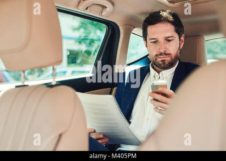 Businessman working in his car during his morning commute - Stock Photo