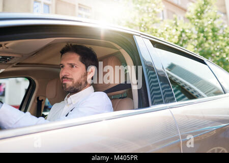 Young man driving his car through city streets - Stock Photo