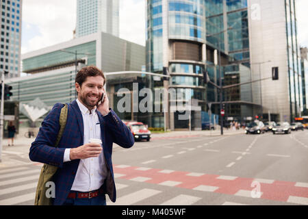 Smiling businessman walking to work on his morning commute - Stock Photo