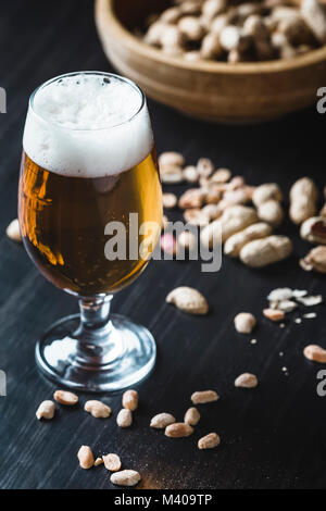 Glass of beer and peanuts on the dark wooden background - Stock Photo
