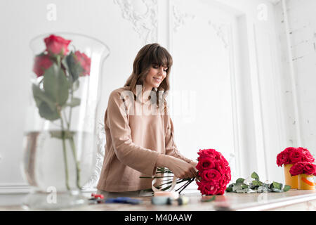 Smiling lovely young woman florist arranging plants in flower shop. People, business, sale and floristry concept. - Stock Photo