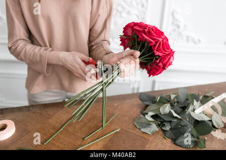 Young woman florist arranging plants in flower shop. People, business, sale and floristry concept. Bouquet of red - Stock Photo
