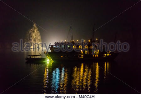 Ships anchored for the night in Halong Bay, North Vietnam. The bay features 3,000  limestone and dolomite karsts - Stock Photo