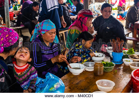 Flower Hmong women eating at the Sunday market at Bac Ha, northern Vietnam. Every Sunday ethnic minorities come - Stock Photo