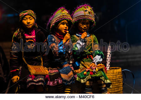 Flower Hmong (hill tribe) girls in traditional costume in Sapa, northern Vietnam. - Stock Photo