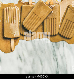 Flatlay of melting coffee latte popsicles, square crop - Stock Photo