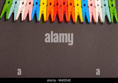 Colorful clothespins on black background - Stock Photo