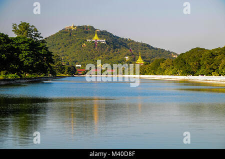 View of Mandalay Hill across the moat by the Royal Palace, Mandalay - Stock Photo