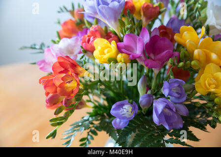 Colorful flower bouquet in a glass bowl on a wooden table - Stock Photo