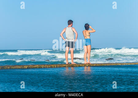 Girl boy teenagers standing on beach ocean tidal swimming pool wall watching waves holiday landscape. - Stock Photo