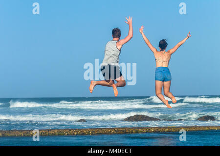 Girl boy teenagers jump leaping on beach ocean tidal swimming pool waves holiday landscape. - Stock Photo