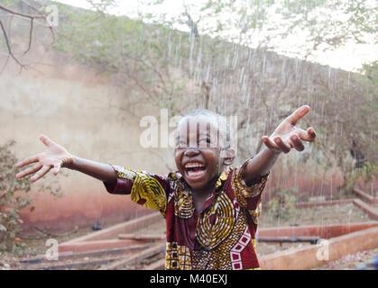 Sweet little African boy under the rain in Mali (Africa) - Stock Photo