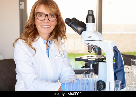 Portrait of a middle aged female physician-scientist using microscope while sitting in laboratory. - Stock Photo