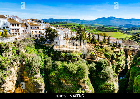 Ronda, Spain: Landscape of white house on the green edges of steep cliffs with mountains in the background. - Stock Photo