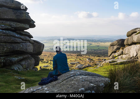 A man comtemplates the view of Dartmoor and beyond from his seat atop Pew Tor, Dartmoor National Park. - Stock Photo
