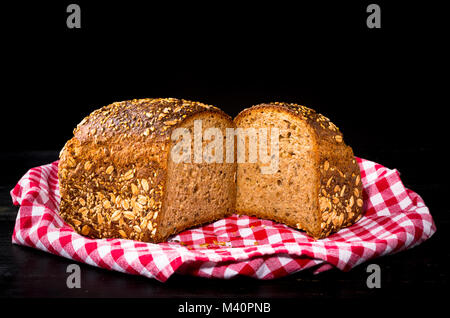 Two halves granary spelt bread on red and white kitchen towel and black wooden background. Front view, closeup. - Stock Photo