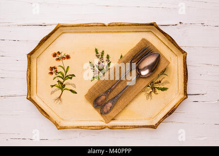 Antique tray with old cutlery spoon and fork  on white wooden background, view from above, flatlay. - Stock Photo