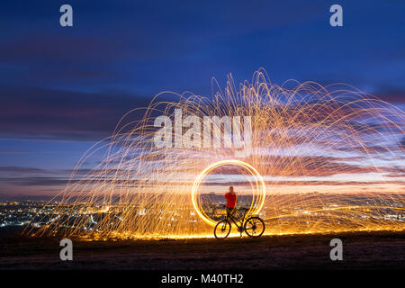 Firework showers of hot glowing sparks from spinning steel wool over night city background. Art show of spinning - Stock Photo