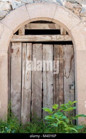 Ancient wooden door in stone wall - Stock Photo
