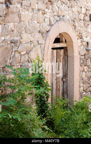 Ancient wooden locked door in stone wall - Stock Photo