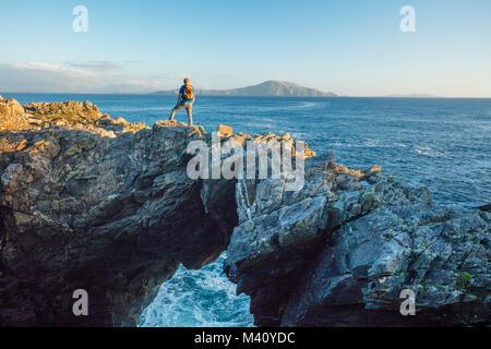Hiker standing on a sea arch, Dooega Head, Achill Island, Co Mayo, Ireland. - Stock Photo
