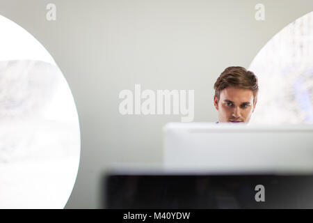 Businessman working on a desktop computer - Stock Photo