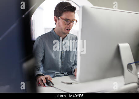 Businessman using mouse on computer - Stock Photo